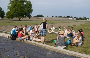 """The participants sitting in the former prisoner's camp (""""Häftlingslager"""") in Sachsenhausen, August 2015. The gravel surfaces in the background depict the area of the barracks. (Photo: Johanna Strunge)"""