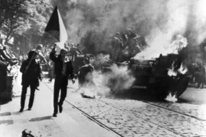 Demonstrators swaying Czech flag rush past a burning Russian tank in front of the building housing Radio Prague, during the continuing protests against the Soviet invasion of their country, August 21, 1968. (Foto: CreativeCommons/CIA)