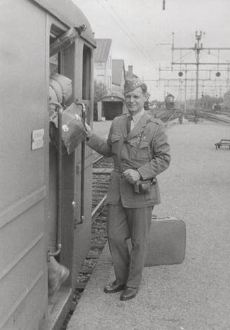 Young man in uniform in next to a train