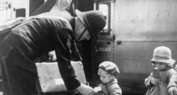 a soldier, a nun and two little girls in front of a train