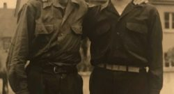 two young men, standing arm in arm